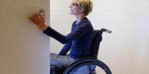 Rollstuhlfahrern öffnet eine Türe