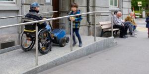 Rollstuhlfahrer auf Rampe bei Gebäudezugang