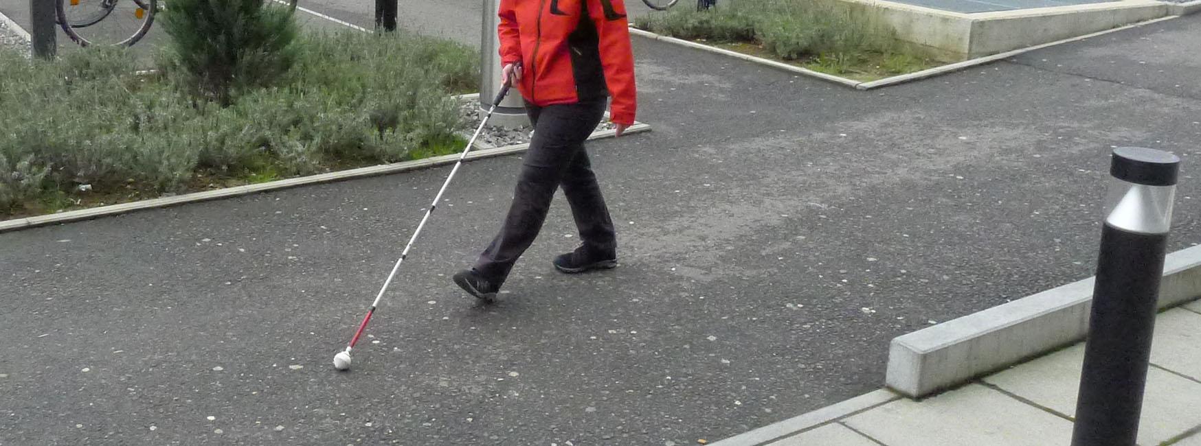 Person mit weissem Stock auf seitlich gut abgegrenztem Fussweg
