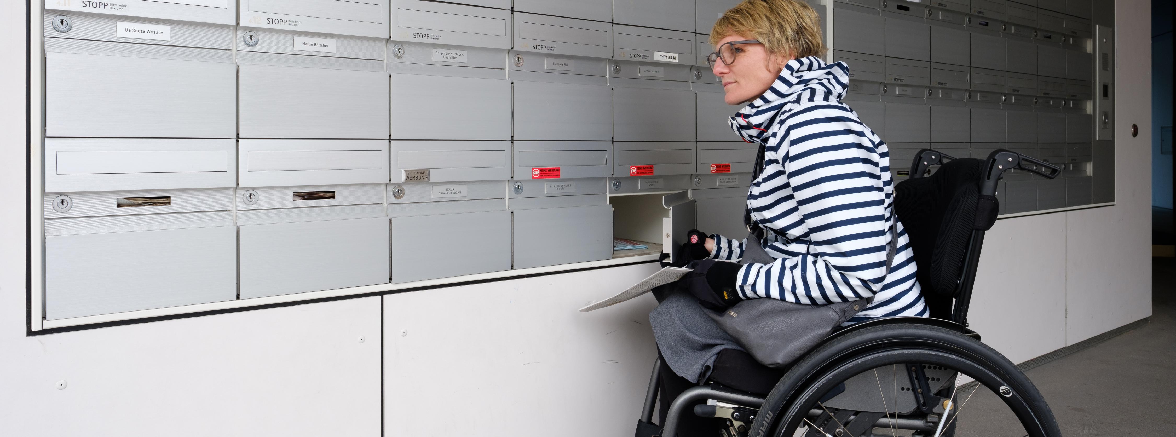 Titelbild: Rollstuhlfahrerin öffnet ihr Fach einer Briefkastenanlage
