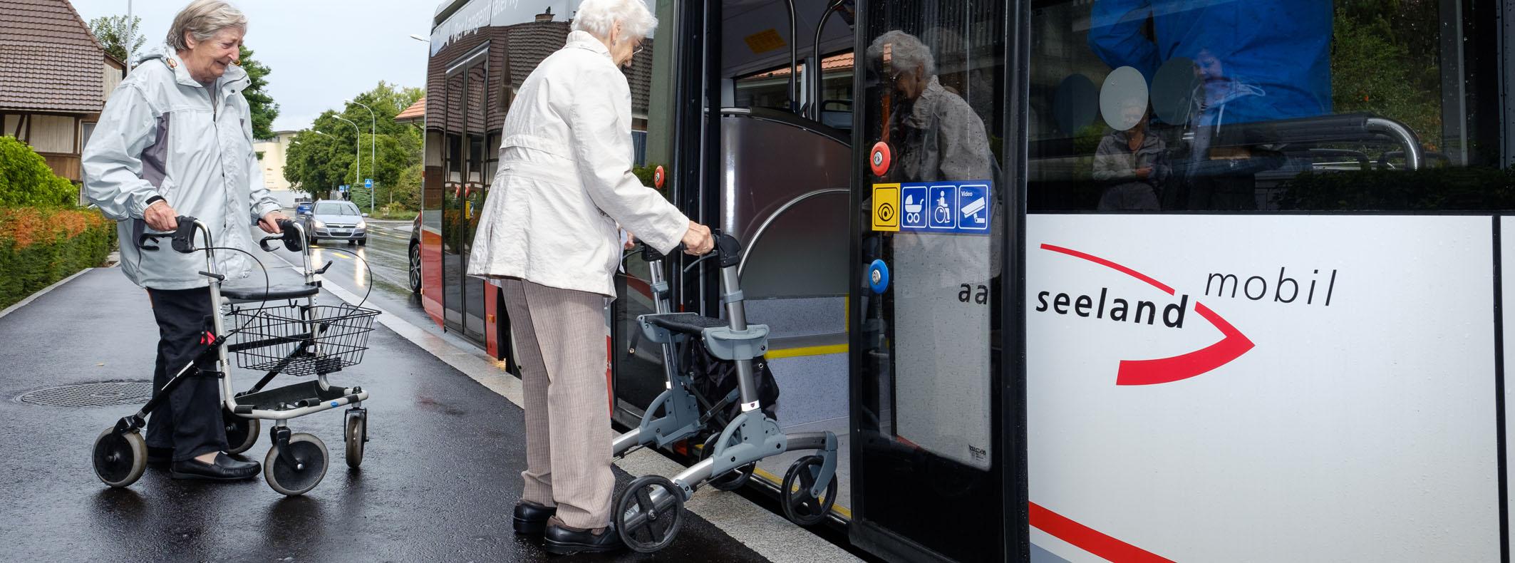 Person mit Rollstuhl beim Einstieg in den Bus an Haltestelle mit hoher Haltekante