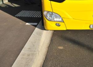 Detail eines Bus an einer hohen Haltekante mit Einkerbung zum Schutz der Karosserie