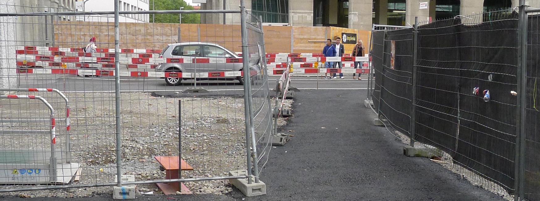 Baustelle mit Absperrgittern und rot-weissen Abschrankingen gegenüber der Fahrbahn