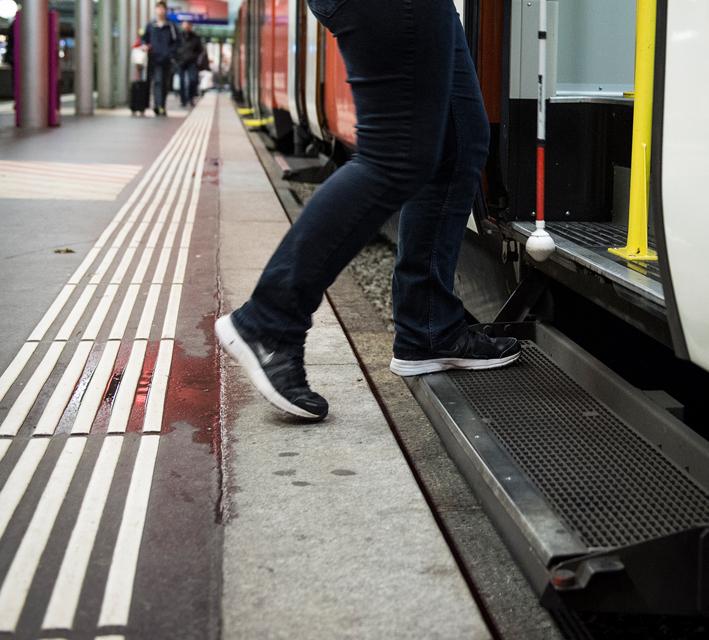 Sicherheitslinie und Person mit weissem Stock beim Einsteigen
